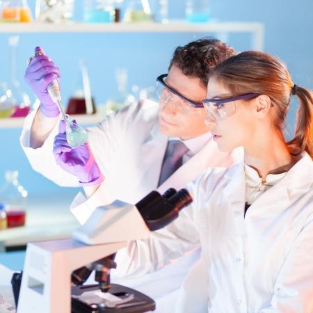 doctoral: Laboratorio chimico scena: attraente giovane studente e il suo post-dottorato supervisore scienziato osservando l'indicatore verde color shift soluzione in bottiglia di vetro. Archivio Fotografico