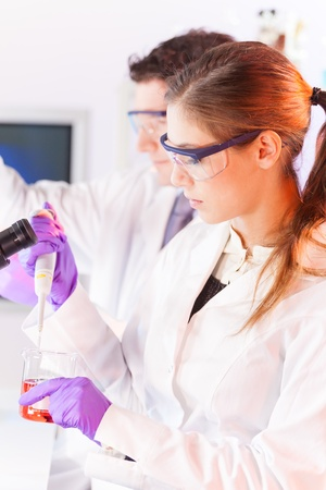 Chemical laboratory scene: attractive young scientist pipetting  red indicator solution. Stock Photo - 17099530