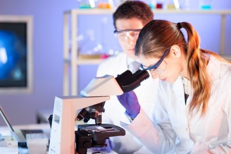 doctoral: Attraente giovane scienziato e il suo supervisore post-dottorato lavorando su un progetto in laboratorio forense.