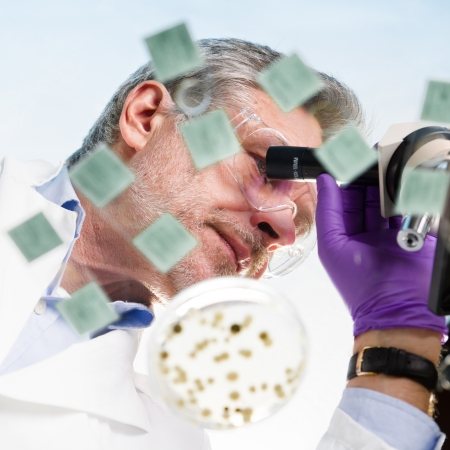 Focused senior life science professional routine screening the microscope slides in the cell laboratory. Lens focus on the researcher's face. photo