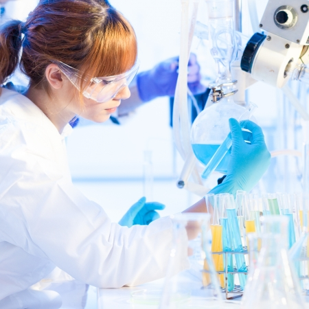 Chemical laboratory scene: attractive young PhD student and her post doctoral supervisor scientist observing the blue indicator color shift after the solution  destillation. Stock Photo - 18174046