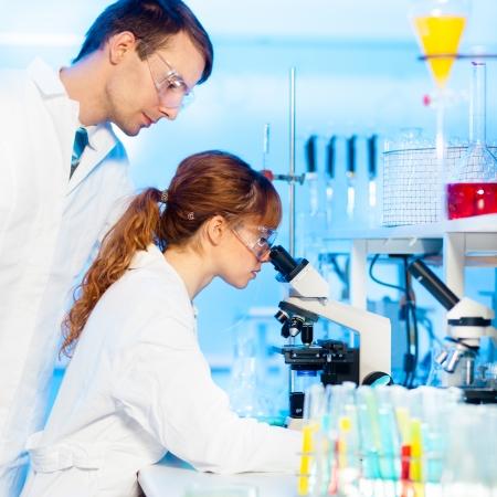 doctoral: Attraente giovane ricercatore femmina e il suo post-dottorato supervisore maschio guardando il vetrino in scienze della vita (medicina legale, microbiologia, biochimica, genetica, oncologia ...) di laboratorio.