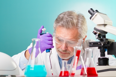 Focused senior life science professional pipetting solution on micro chip.  Lens focus on the face of the researcher. Stock Photo - 18153171