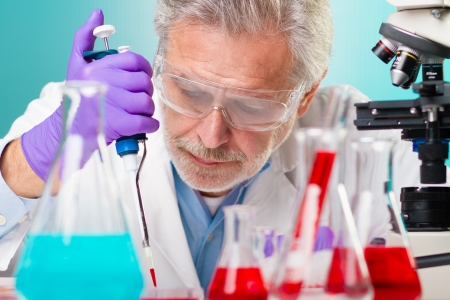 Focused senior life science professional pipetting solution on micro chip.  Lens focus on the researcher's face. Stock Photo - 18153168