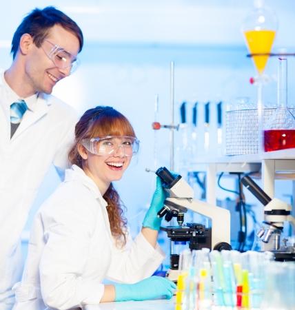doctoral: Attraente giovane ricercatore femmina e il suo post-dottorato supervisore maschio divertirsi guardando il vetrino da microscopio in laboratorio delle scienze della vita.