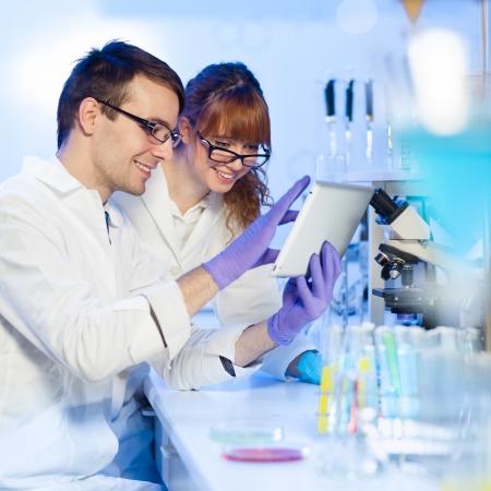 doctoral: Attraente giovane ricercatore femmina e il suo post-dottorato supervisore maschio guardando la tavoletta in scienze della vita (medicina legale, microbiologia, biochimica, genetica, oncologia ...) di laboratorio.