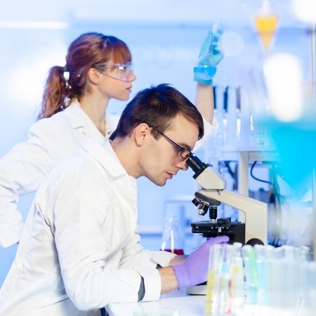 investigador cientifico: Investigador de sexo masculino joven que mira en el portaobjetos en la ciencia de la vida (medicina forense, microbiolog�a, bioqu�mica, gen�tica, oncolog�a ...) de laboratorio. Cient�fico asistant Mujer trabajando en segundo plano.