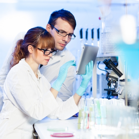 medical education: Attractive young female research scientist and her post doctoral male supervisor looking focused at the tablet in the life science (forensics, microbiology, biochemistry, genetics, oncology...)laboratory.