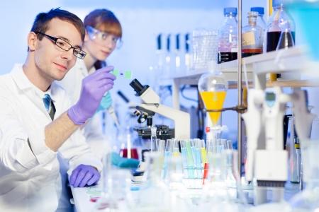 bata de laboratorio: Investigador de sexo masculino joven que mira en el portaobjetos en la ciencia de la vida (medicina forense, microbiología, bioquímica, genética, oncología ...) de laboratorio. Científico asistant Mujer trabajando en segundo plano.