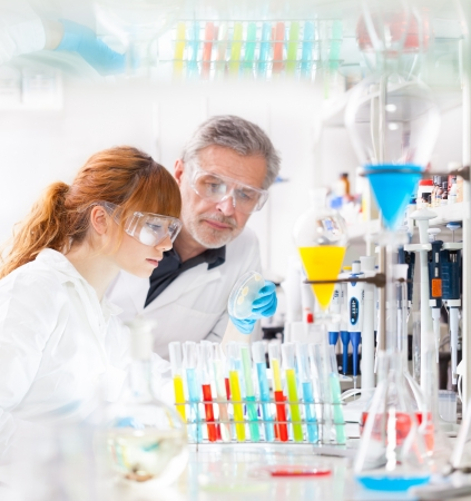 Attractive young female scientist and her senior male supervisor looking at the cell colony grown in the petri dish in the life science research laboratory (bichemistry, genetics, forensics, microbiology..) Stock Photo - 18355502