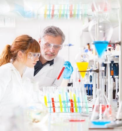bata de laboratorio: Atractiva mujer joven cient�fico y su supervisor senior masculino observando el cambio de color de un l�quido rojo en el tubo de vidrio en el laboratorio de investigaci�n de ciencias de la vida (bichemistry, la gen�tica, la medicina forense, microbiolog�a ..)