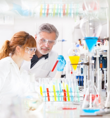 pharmacy equipment: Attractive young female scientist and her senior male supervisor observing color shift of a red liquid in the glass tube in the life science research laboratory (bichemistry, genetics, forensics, microbiology..) Stock Photo