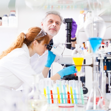 Attractive young female scientist and her senior male supervisor looking at the microscope slide in the life science research laboratory (bichemistry, genetics, forensics, microbiology..) Stock Photo - 18355497