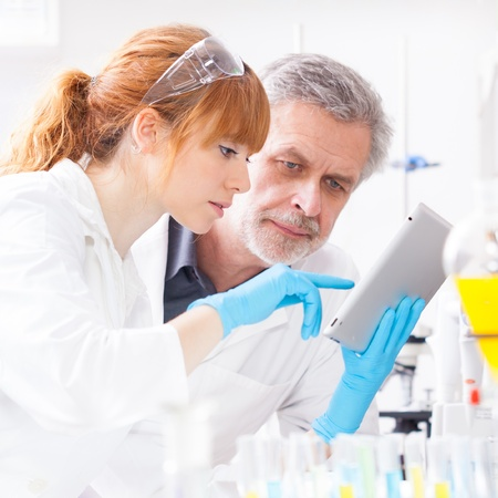 Attractive young female scientist and her senior male supervisor checking experiment protocol at tablet laptop computer in the life science research laboratory (bichemistry, genetics, forensics, microbiology..)