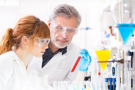 Attractive young female scientist and her senior male supervisor observing color shift of a red liquid in the glass tube in the life science research laboratory (bichemistry, genetics, forensics, microbiology..) Stock Photo - 18355487