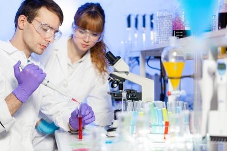 material de vidrio: Investigador joven macho pipeteo líquido rojo en el tubo de vidrio en el laboratorio (análisis forense, microbiología, bioquímica, genética, oncología ...). Estudiante femenino ciencia asistant observando y aprendiendo el protocolo.