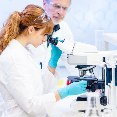 Attractive young female scientist and her senior male supervisor looking at the microscope slide in the life science research laboratory (biochemistry, genetics, forensics, microbiology..) Stock Photo - 18355488