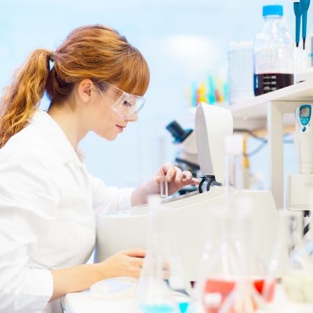 Enfocada atractivo joven ciencias de la vida profesional midiendo la absorbancia de la solución en la cubeta en el espectrofotómetro. Foco en la cara del investigador.