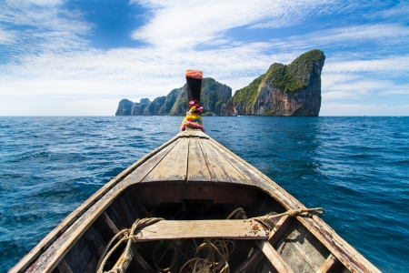 approaching: Traditional wooden  boat approaching picture perfect tropical Koh Phi Phi island, Thailand, Asia.