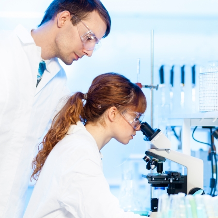 doctoral: Attractive young female research scientist and her post doctoral male supervisor looking at the microscope slide in the life science (forensics, microbiology, biochemistry, genetics, oncology...)laboratory.