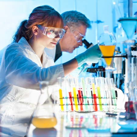 pharmacy equipment: Attractive young female scientist and her senior male supervisor pipetting and microscoping in the life science research laboratory (biochemistry, genetics, forensics, microbiology..) Stock Photo