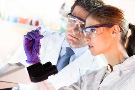 examenes de laboratorio: Cient�fico joven y atractiva y su suprvisor mirando el portaobjetos de un microscopio en el laboratorio forense Foto de archivo