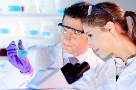 doctoral: Chemical laboratory scene  attractive young student and her post doctoral supervisor scientist observing the green indikator solution color shift in glass flask  Stock Photo