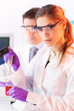 Chemical laboratory scene  attractive young scientist pipetting  red indikator solution Stock Photo - 19800270