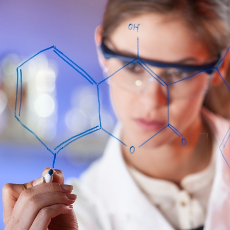 wise woman: Portrait of a confident female health care professional in his working environment writing structural chemical formula on a glass board