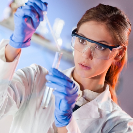Focused young life science professional pipetting solution into the glass cuvette  Lens focus on the researcher Stock Photo
