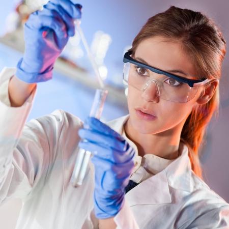 Gericht jonge life science professional pipetteren oplossing in het glas cuvet Lens gericht op de onderzoeker