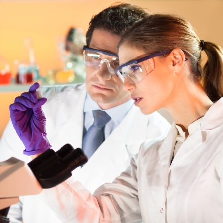Attractive young scientist and her post doctoral supervisor looking at the microscope slide in the forensic laboratory Stock Photo - 19800241