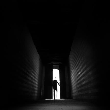 La silhouette della persona che entra nel corridoio retroilluminato