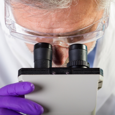 medical technical equipment: Focused senior life science professional routine screening the microscope slides in the cell laboratory