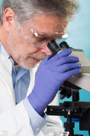 creativ: Focused senior life science professional routine screening the microscope slides in the cell laboratory. Stock Photo