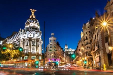 via: Rays of traffic lights on Gran via street, main shopping street in Madrid at night. Spain, Europe.