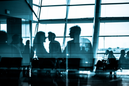 Silhouettes of business people traveling on airport; waiting at the plane boarding gates  photo