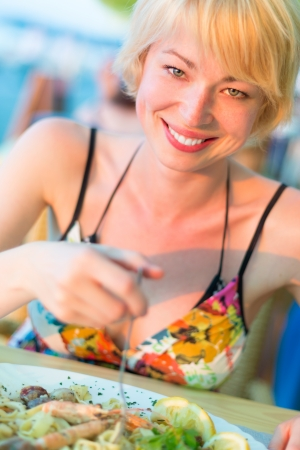 Closeup of a cheerful young woman eating healthy mediterranean sea food meal on the outdoor restaurant terrace. photo