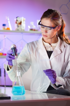 pharmacy technician: Focused young life science professional pipetting solution into the glass cuvette. Lens focus on the researchers eye. Stock Photo
