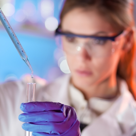 pharmacy technician: Focused life science professional pipetting solution into the glass cuvette. Lens focus on the drop.