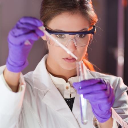 pipeta: Joven ciencia solución enfocada vida profesional pipeta en la cubeta de vidrio. Foco de la lente en el ojo del investigador.