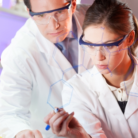 writing on glass: Portrait of a focused health care professionals in their working environment writing structural chemical formula on a glass board. Stock Photo