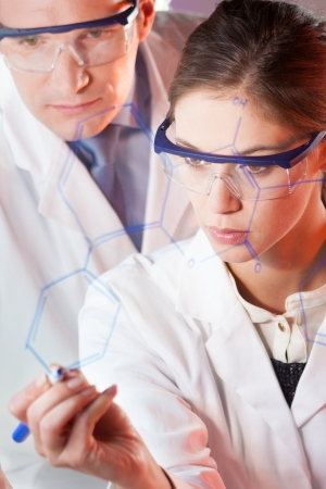 medical research: Portrait of a focused health care professionals in their working environment writing structural chemical formula on a glass board. Stock Photo