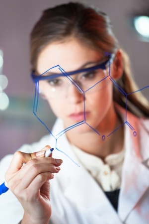 writing on glass: Portrait of a confident female health care professional in his working environment writing structural chemical formula written on a glass board. Stock Photo