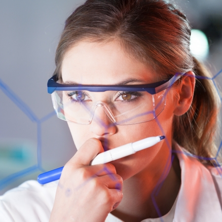 dental research: Portrait of a confident female health care professional in his working environment reviewing structural chemical formula written on a glass board.