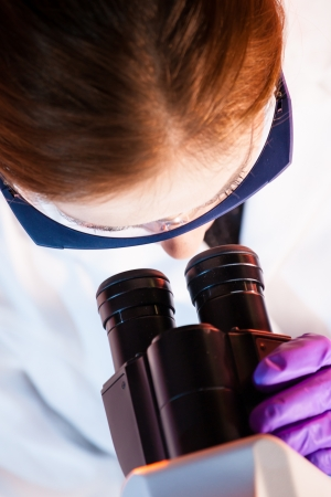 Scientist looking trough the microscope. Stock Photo - 20680328