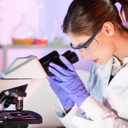 dental research: Close up portrait of a attractive, young, female health care professional microscoping.