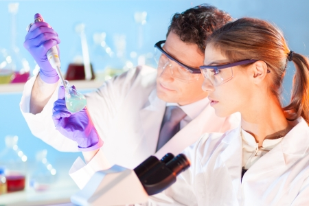 Chemical laboratory scene: attractive young student and her post doctoral supervisor scientist observing the green indikator solution color shift in glass flask. Stock Photo - 20680093