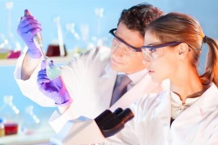laboratorio: Laboratorio qu?mico escena: Estudiante atractivo joven y su director de tesis cient?fico posterior observaci?n de la soluci?n verde indikator cambio de color en frasco de vidrio.