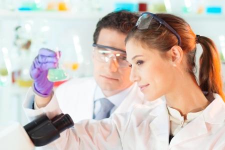 doctoral: Laboratorio chimico scena: attraente giovane studente e il suo supervisore di dottorato scienziato posto osservando il verde soluzione cambiamento indikator colore in bottiglia di vetro. Archivio Fotografico